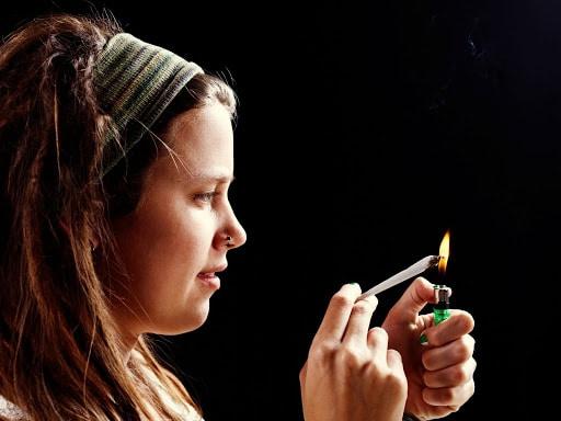 Žena koja pati od zavisnosti od kanabisa priprema se za pušenje trave zbog povlačenja simptoma apstinencijalne krize.